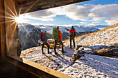 Hikers admiring sunrise from an alpine hut, Livigno, Valtellina, Italy