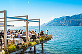 Malcesine, lake Garda, Verona province, Veneto, Italy, Tourists eating out in a restaurant on water