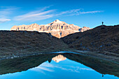 Hiker in silhouette near a small pond with Sella group with the highest Piz Boè mountain reflected, Pordoi pass, Arabba, Beuuno, Veneto, Italy