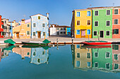 colorful houses in Burano reflected in the water canal, Venice, Veneto, Italy