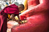 Swayambhunath,Katmandu,Nepal Young monk painting the statue at Swayambhunath temple