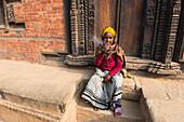 Patan durbar square,Katmandu,Nepal Woman smokes in the Patan square