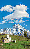 Panorama of church and meadows framed by snowy peak of Pizzo di Prata Daloo Chiavenna Valley Valtellina Lombardy Italy Europe