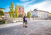 A couple of tourists walking in Ljubljiana old town, with the iconic Franciscan Annunciation church on the background, Ljubljiana, Osrednjeslovenska, Slovenia