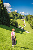A girl in Typical Bayern dress walking in front of Wamberg village, with Mount Zugspitze and Waxenstein on the background, Garmisch Partenkirchen, Bayern, Germany