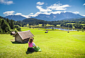 A girl in typical dress looks at the Geroldsee, Gerold, Garmisch Partenkirchen, Bayern, Germany