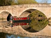 Red narrow boat passes under Shillingford Bridge reflected in River Thames, Shillingford, Oxfordshire, England, United Kingdom, Europe