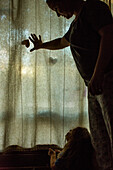 Caucasian mother and daughter looking at window curtain