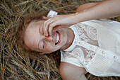Smiling Caucasian girl with freckles laying in wheat