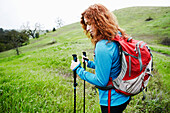 Caucasian woman hiking with walking sticks