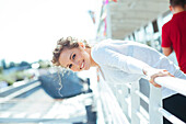 Smiling Caucasian woman leaning over railing