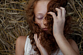 Caucasian girl laying in wheat holding hair