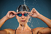 Water splashing on Caucasian woman adjusting swimming goggles