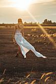 Sexy Caucasian woman wearing white dress walking in field