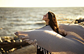 Wind blowing shawl of Caucasian woman at beach