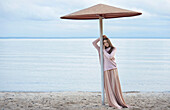 Pensive Caucasian woman leaning on beach umbrella