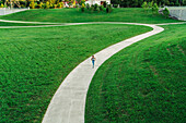 Distant mixed race woman running on winding path in park