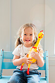 Smiling Caucasian girl holding rubber chicken
