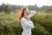 Wind blowing hair of Caucasian woman in field
