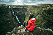 Caucasian woman sitting on cliff admiring waterfall