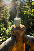 Steaming coffee cup on wooden post
