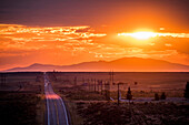 Cars driving on remote road at sunset