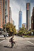stylish New Yorker with Iroquois sitting on a racing bike in front of ONE World Trade Center and looking at mobile phone, Manhattan, NYC, New York City, United States of America, USA, North America