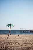 beach shower camouflaged as coconut palm tree on the beach of Coney Island, Steeplechase Pier in background, Brooklyn, NYC, New York City, United States of America, USA, North America