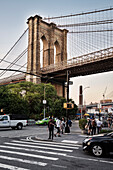 pedestrian looking at a mobile phone at a zebra crossing, in front of Brooklyn Bridge, Brooklyn, NYC, New York City, United States of America, USA, North America