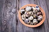 Quail eggs in a wooden plate, top view