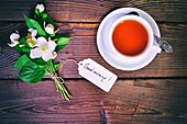 Cup of tea and a bouquet of blossoming jasmine with a paper tag, a good morning inscription