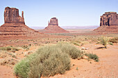 The green of desert sage brush contrasts with the iconic, orange colored sandstone formations in Monument Valley.