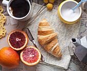High Angle View of Croissant, Blood Oranges, Cup of Tea and Yellow Sugar Bowl