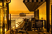 Bainbridge Ferry and seagulls on Pier 54 during the golden hour before sunset, Alaskan Way, Downtown, Seattle, Washington State, United States of America, North America