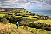 Walker on the South West Coast Path near Stonebarrow with Golden Cap in distance, Charmouth, Jurassic Coast, UNESCO World Heritage Site, Dorset, England, United Kingdom, Europe