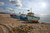 Three small fishing boats pulled up on shingle beach, Beer, Devon, England, United Kingdom, Europe