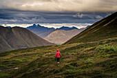 Lone hiker walks into Alaskan wilderness, Alaska, United States of America, North America