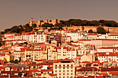 View over the old town to Castelo de Sao Jorge castle at sunset, Lisbon, Portugal, Europe