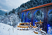 Snowy Christmas market under a railway viaduct, illuminated, Ravennaschlucht, Höllental near Freiburg im Breisgau, Black Forest, Baden-Württemberg, Germany