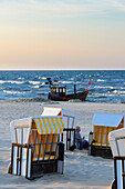 Woman leaning against beach chair and small wooden fishing boat in the background of Ahlbeck, Usedom, Ostseeküste, Mecklenburg-Western Pomerania, Germany