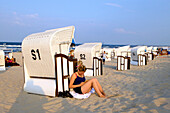 Young woman is leaning against a beach chair, reading a book, Strand, Bansin, Usedom, Ostseeküste, Mecklenburg-Vorpommern, Germany