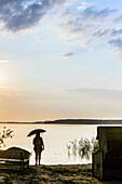 Frau Steht mit Regenschirm im Gegenlicht am Ufer auf der Boddenseite im Lieper Winkel, Usedom, Ostseeküste, Mecklenburg-Vorpommern, Deutschland