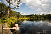 Bathing old lady in lake Tiefsee at the foothill of the bavarian alps, Saulgrub, Upper Bavaria, Germany