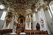 Two visitors admire the overwhelming art of the Wieskirche, Steingaden, Upper Bavaria, Germany