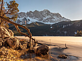 A sunny winter afternoon at the frozen Eibsee with a view of the Zugspitze and the Zugspitzbahn, Eibsee, Upper Bavaria, Germany