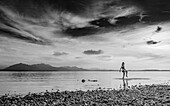 A girl walks through the Chiemsee on a summer evening,in the background the Chiemgau Alps, Chieming, Upper Bavaria, Germany