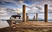 View of a boat on a jetty, in the background the Fraueninsel and the Chiemgau Alps on a summer evening, Gstadt am Chiemsee, Upper Bavaria, Germany