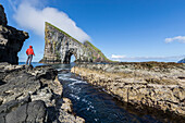 Man on cliffs looks towards the natural arch of Drangarnir rock, Vagar Island, Faroe Islands, Denmark, Europe