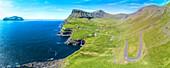 Panoramic of the road in between meadows and ocean, Gasadalur, Vagar Island, Faroe Islands, Denmark, Europe