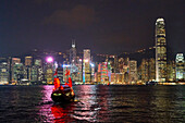 Traditional junk boat on Victoria Harbour with city skyline behind illuminated at night, Hong Kong, China, Asia